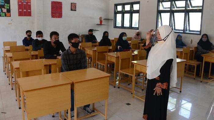 Seorang guru memberikan arahan kepada murid baru dalam ruangan kelas dengan pembatasan jaga jarak saat simulasi penerapan protokol kesehatan di SMA-1 Banda Aceh, Aceh, Sabtu (11/7/2020). Sebagian SMA/SMK di daerah itu menyatakan siap memulai Proses Belajar Mengajar (PBM) tahun ajaran baru 2020/2021 yang dijadwalkan pada, Senin (13/7/2020), baik secara tatap muka maupun daring dengan penerapan prorokol kesehatan guna mencegah penyebaran COVID-19, namun hingga saat ini pihak sekolah masih menunggu keputusan dari pemerintah. ANTARA FOTO/Ampelsa/hp.