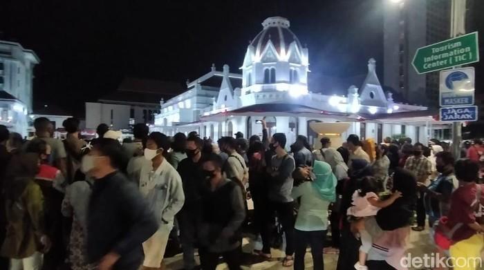 Ratusan pengunjung Alun-alun Suroboyo memenuhi pedestrian Jalan Gubernur Suryo hingga Yos Sudarso. Mereka tak bisa masuk alun-alun karena ada pembatasan pengunjung.