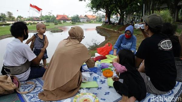 Tampak sejumlah keluarga membawa tikar serta bekal makanan untuk makan siang bersama keluarga di taman yang berada di kawasan objek wisata TMII.