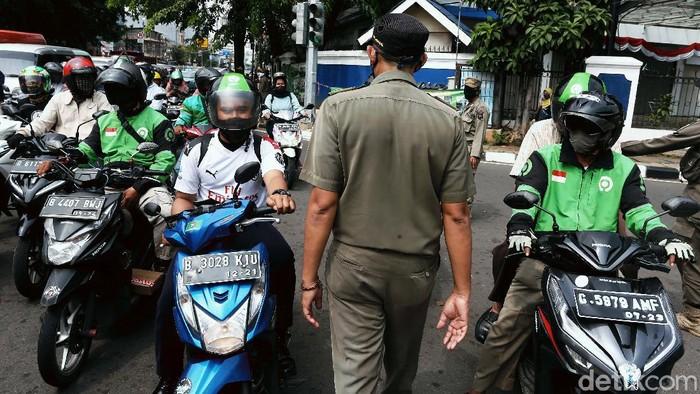Meski di hari libur, petugas Satpol PP tetap menggelar razia bagi pengendara yang tak menggunakan masker. Razia dilakukan di jalan Proklamasi, Jakarta, Kamis (20/8).
