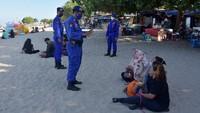 Sejumlah polisi pun melakukan pengawasan dan memberikan teguran kepada para wisatawan yang tak mengenakan masker dan tak menerapkan protokol kesehatan saat berwisata di pantai tersebut. ANTARA FOTO/Nyoman Hendra Wibowo.