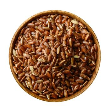 Wooden bowl with uncooked brown rice isolated on white background. Top view