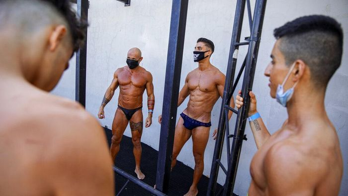 Contestants prepare backstage during the National Amateur Body Builders Association competition in Tel Aviv, Israel, Wednesday, Aug. 19, 2020. Because of the coronavirus pandemic, this years competition was staged outdoors in Tel Aviv. The 85 participants were required to don protective masks in line with health codes. (AP Photo/Oded Balilty)