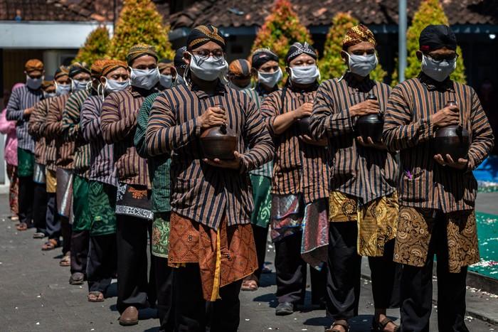 Pasukan Patangpuluh Kendi Kasepuhan Girikusumo dengan mengenakan masker mengirab kendi berisi air dari sumur berkah Girikusumo sebagai simbol berkah alam dalam prosesi Tradisi Kirab Sura Girikusumo di Desa Banyumeneng, Mranggen, Demak, Jawa Tengah, Kamis (20/8/2020). Tradisi menyambut tahun baru Islam 1 Muharram 1442 Hijriyah atau satu Sura yang biasanya dihadiri ribuan warga itu, kali ini hanya dihadiri keluarga besar Kasepuhan Girikusumo dengan menerapkan sejumlah protokol kesehatan guna mencegah penyebaran COVID-19. ANTARA FOTO/Aji Styawan/aww.