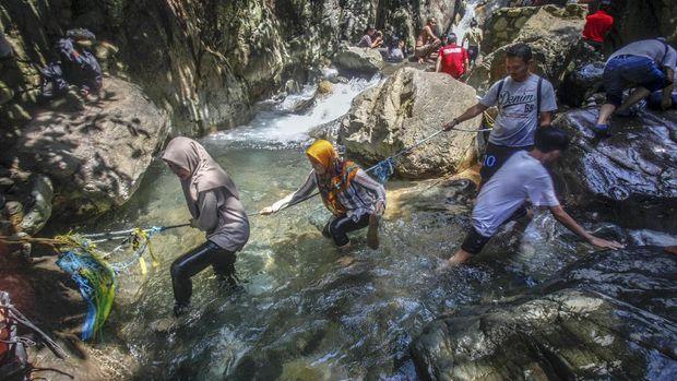 Sejumlah wisatawan menikmati air terjun Leuwi Hejo di Babakan Madang, Kabupaten Bogor, Jawa Barat, Jumat (21/8/2020). Wisata air terjun Leuwi Hejo menjadi salah satu tujuan wisata alam di Bogor pada libur Tahun Baru Islam 1 Muharam 1442 Hijriah dan libur akhir pekan. ANTARA FOTO/Yulius Satria Wijaya/pras.