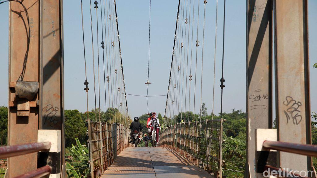 Warga melintas di jembatan gantung di Curug, Depok, Jabar. Jembatan yang membentang di atas Kali Angke tersebut menghubungkan Depok dengan Bogor.