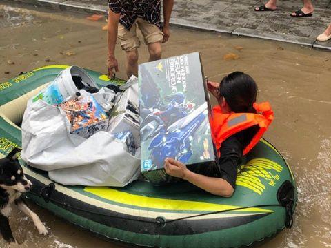 Wanita menyelamatkan mainan suami dari banjir.