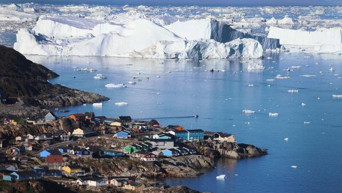 ILULISSAT, GREENLAND - JULY 30: An iceberg floats in Disko Bay behind houses during unseasonably warm weather on July 30, 2019 in Ilulissat, Greenland. The Sahara heat wave that recently sent temperatures to record levels in parts of Europe is arriving in Greenland. Climate change is having a profound effect in Greenland, where over the last several decades summers have become longer and the rate that glaciers and the Greenland ice cap are retreating has accelerated.   (Photo by Sean Gallup/Getty Images)