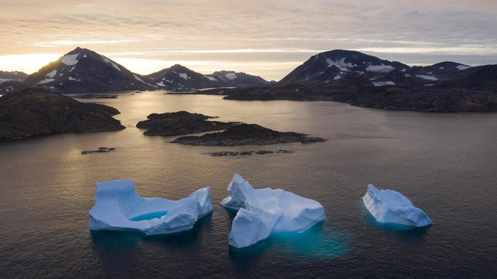FILE - In this Aug. 16, 2019 file photo, icebergs float away as the sun rises near Kulusuk, Greenland. According to a study released on Thursday, Aug. 20, 2020, Greenland lost a record amount of ice during an extra warm 2019, with the melt massive enough to cover California in more than four feet (1.25 meters) of water. (AP Photo/Felipe Dana, File)