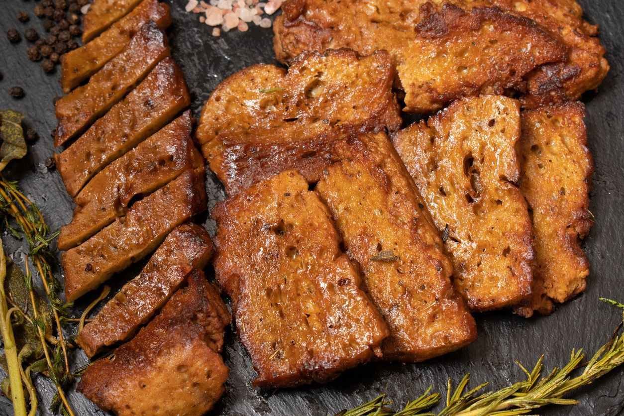 Plate of Seitan, wheat gluten, with green salad. Seitan is a meat substitute in the vegetarian and vegan cuisine.