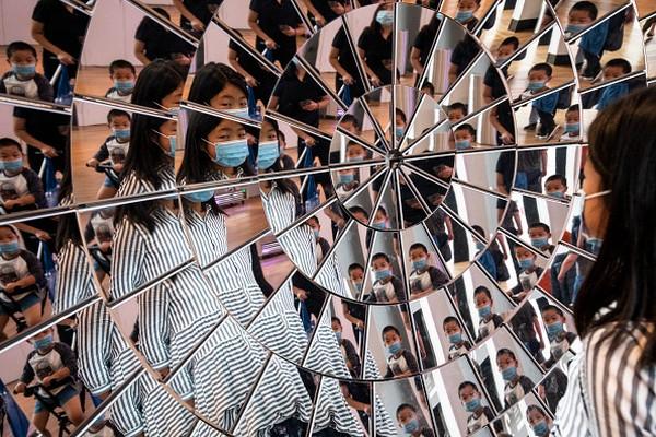 Anak-anak bermain di objek cermin besar di Science Museum di London, Inggris.