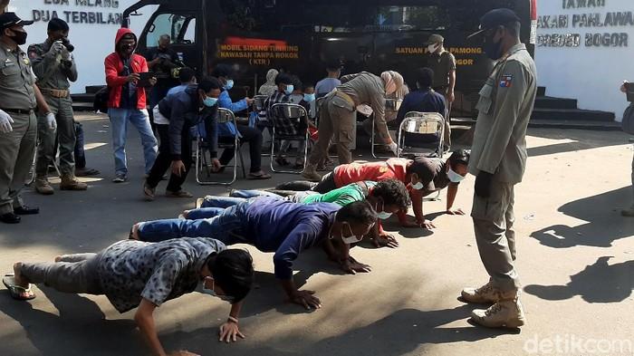 Sejumlah sopir angkot terjaring razia masker di Bogor. Para sopir angkot itu pun dihukum push up karena tak mengenakan masker saat beraktivitas di tempat umum.