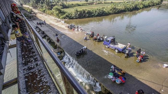 Sejumlah warga mencuci pakaian di aliran Sungai Cileungsi, Citeureup, Bogor, Jawa Barat, Selasa (25/8/2020). Musim kemarau membuat sebagian warga di kawasan tersebut terpaksa mencuci dan mandi di air sungai karena sumur di rumah mereka kering. ANTARA FOTO/Yulius Satria Wijaya/foc.