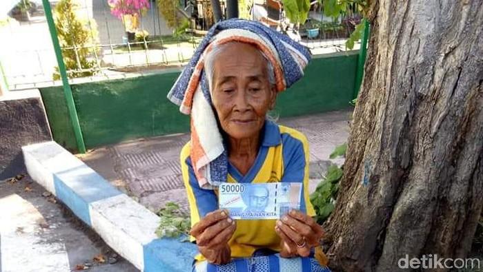 Nenek penjual mangga di Bali dibayar menggunakan uang mainan (Angga Riza/detikcom)