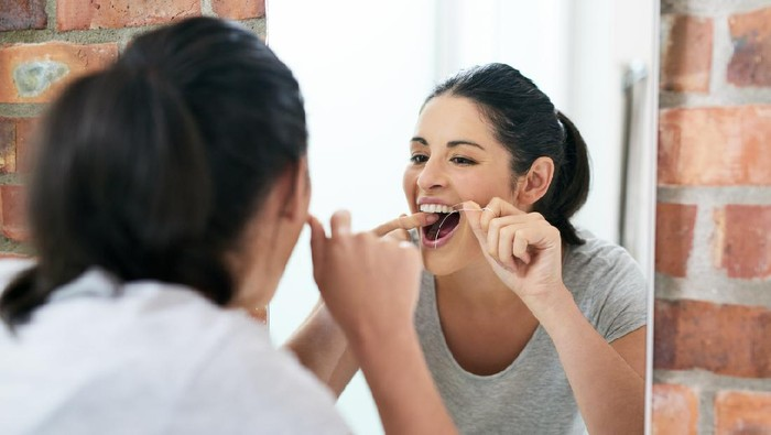 Shot of a beautiful young woman flossing her teeth in the bathroom mirror