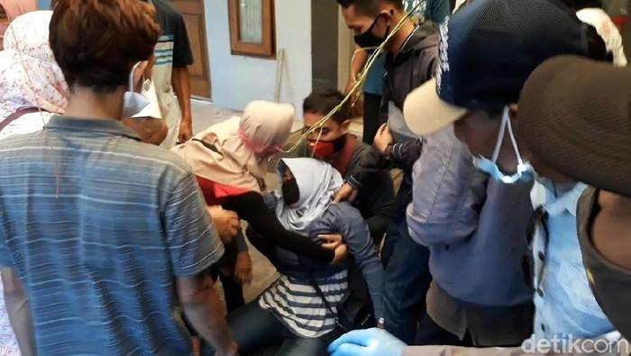 Garis polisi di rumah korban pembunuhan empat orang sekeluarga di Sukoharjo telah dicopot oleh polisi, Rabu (26/8/2020). Kerabat korban diperbolehkan masuk untuk membersihkan rumah korban. Namun tiba-tiba salah satu kerabat korban menangis tersedu dan terkulai lemas. Perempuan tersebut akhirnya diangkat oleh saudaranya.