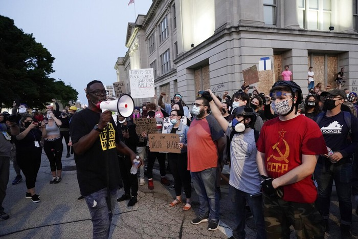 A protester holds up a phone as he stands in front of authorities Tuesday, Aug. 25, 2020, in Kenosha, Wis. Anger over the Sunday shooting of Jacob Blake, a Black man, by police spilled into the streets for a third night. (AP Photo/Morry Gash)