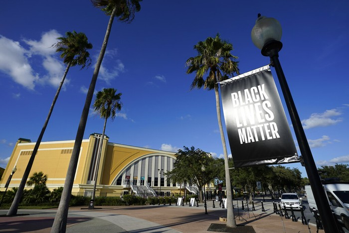 A Black Lives Matter banner hangs outside of the arena after a postponed NBA basketball first round playoff game between the Milwaukee Bucks and the Orlando Magic, Wednesday, Aug. 26, 2020, in Lake Buena Vista, Fla. The game was postponed after the Milwaukee Bucks didn't take the floor in protest against racial injustice and the shooting of Jacob Blake, a Black man, by police in Kenosha, Wisconsin. (AP Photo/Ashley Landis, Pool)