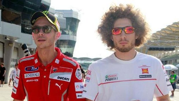 Honda rider Marco Simoncelli of Italy (R) and Ducati rider Valentino Rossi of Italy (L) chat before the MotoGP pre-season second test run on the Sepang circuit near Kuala Lumpur on February 23, 2011. The MotoGP season will start in Qatar on March 20. AFP PHOTO / KAMARUL AKHIR (Photo by KAMARUL AKHIR / AFP)