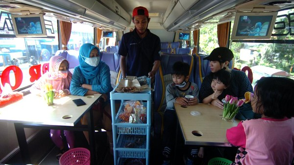 Pelayan menawarkan makanan dan minuman kepada pengunjung angkringan on the bus di Pemalang, Jawa Tengah, Jumat (28/8/2020).