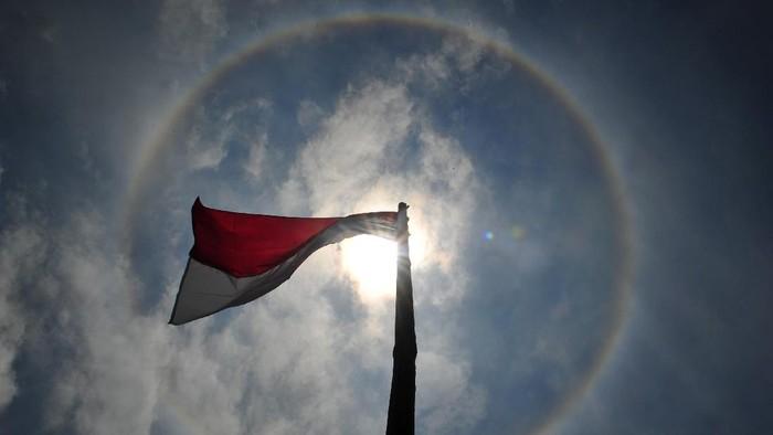 Bendera merah putih berkibar saat terjadinya Halo Matahari di Kayu Aro Barat, Kerinci, Jambi, Jumat (28/8/2020). Halo Matahari merupakan fenomena optis berupa lingkaran cahaya di sekitar matahari yang terjadi karena uap air yang terkandung di awan bereaksi dengan sinar matahari. ANTARA FOTO/Wahdi Septiawan/wsj.