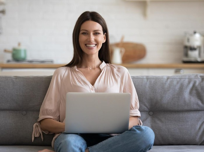 Portrait of smiling businesswoman sitting alone on comfortable sofa at home with computer on knees. Happy female freelancer working remotely in own house, posing for photo, looking at camera.