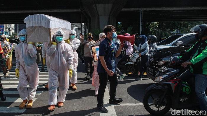 Petugas dari kecamatan Cilandak membawa peti mati di jalan Fatmawati, Jakarta, Jumat (28/8/2020). Kegiatan tersebut untuk mensosialisasikan bahaya Covid-19 yang dapat menyebabkan kematian. Kampanye unik ini juga diikuti oleh TNI, Polri dan dinas terkait di lingkungan Pemprov DKI.