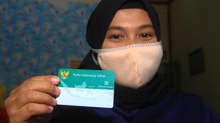 Warga Desa Madusari Nur Sufianti memperlihatkan Kartu Indonesia Sehat (KIS) miliknya saat hendak berobat di Puskesmas Sungai Durian di Kecamatan Sungai Raya, Kabupaten Kubu Raya, Kalimantan Barat, Jumat (28/8/2020). Layanan pengobatan yang diterima peserta Jaminan Kesehatan Nasional-Kartu Indonesia Sehat (JKN-KIS) di puskesmas tersebut merupakan wujud nyata dari hadirnya pemerintah dalam menjamin pelayanan kesehatan masyarakat Indonesia. ANTARA FOTO/Jessica Helena Wuysang/wsj.k