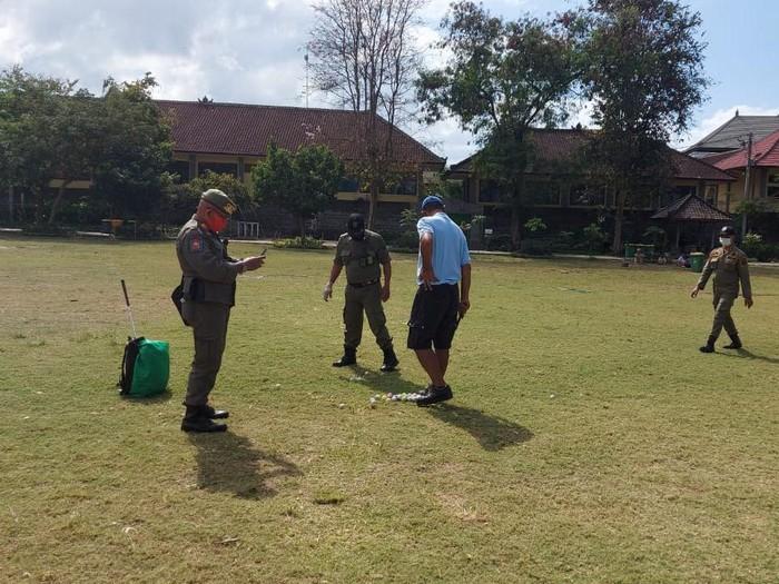 Seorang pria main golf di Taman Lumintang, Denpasar, Bali.