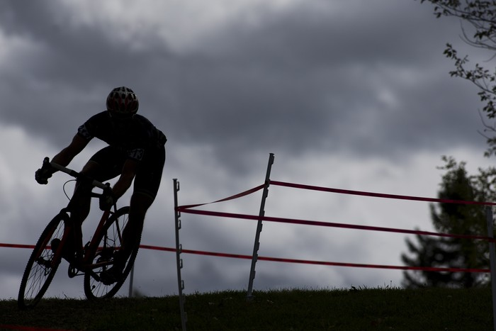 Athlete on racing bike outdoors at sunset, close-up