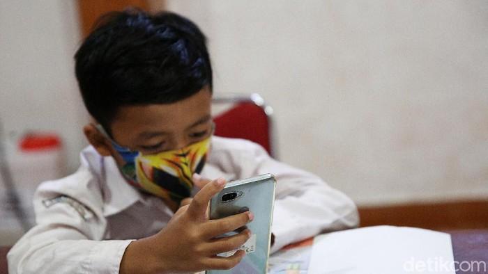 Siswa siswi menggunakan fasilitas WiFi gratis saat mengikuti kegiatan pembelajaran jarak jauh di balai warga RW 05 Kelurahan Kuningan Barat, Mampang Prapatan, Jakarta, Jumat (27/8/2020). WiFi gratis ini disediakan oleh swadaya warga RW 05 guna membantu anak-anak yang melakukan pembelajaran jarak jauh yang terkendala dengan kuota internet.