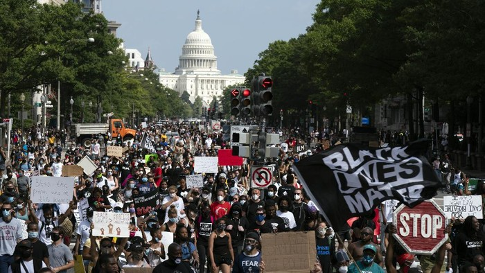 People walk on Pennsylvania Avenue during the March on Washington, Friday Aug. 28, 2020, on the 57th anniversary of the Rev. Martin Luther King Jr.s I Have A Dream speech. (AP Photo/Jose Luis Magana)