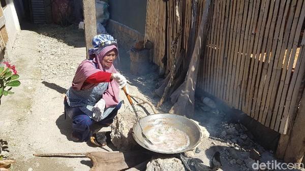 Seorang ibu membuat minyak kelapa scara tradisional di desa di kawasan Pantai Labuang. (Abdy Febriady/detikTravel)