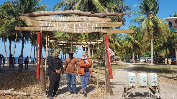 Pengunjung berfoto di depan gerbang wisata Pantai Labuang. (Abdy Febriady/detikTravel)