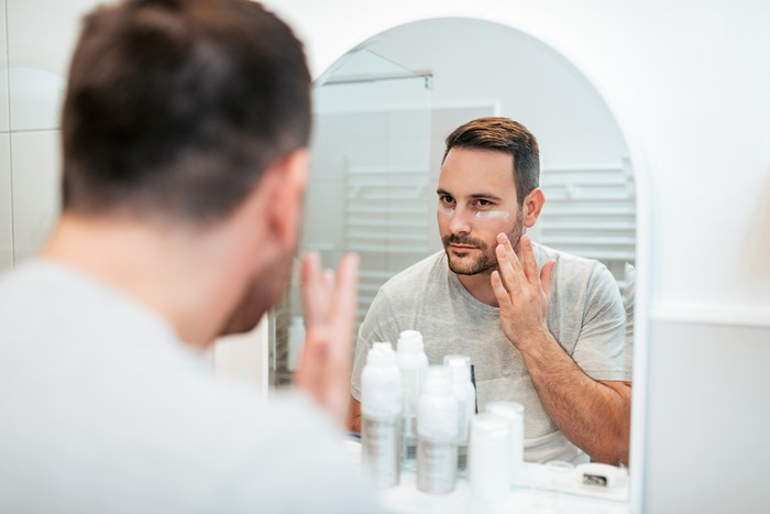 Handsome man applying face cream in the bathroom.