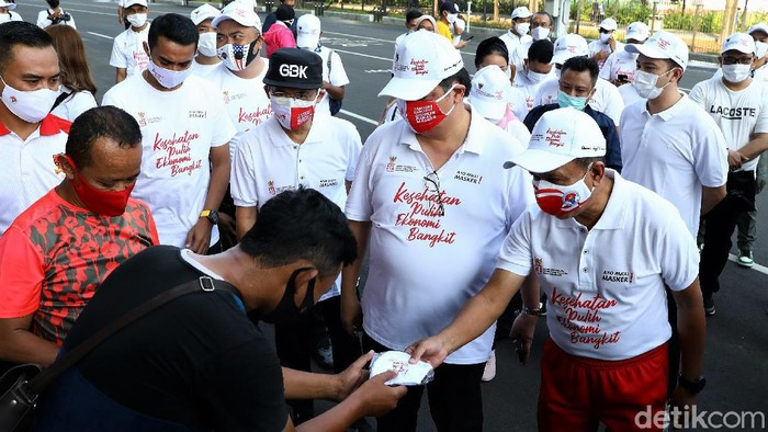 Sosialisasi dan aksi bagikan masker digelar di Gelora Bung Karno, Jakarta. Menko Perekonomian Airlangga Hartarto dan Menpora Zainuddin Amali hadir di acara itu.