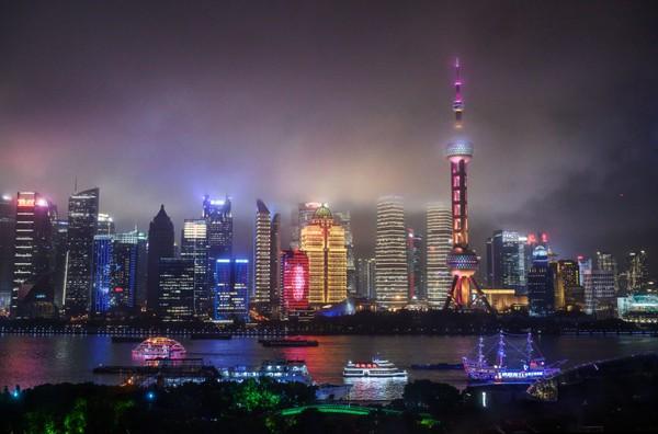 Perahu berjalan di Sungai Huangpu saat cakrawala kota terlihat, termasuk Menara TV Oriental Pearl dan Menara Shanghai, di Shanghai, China.