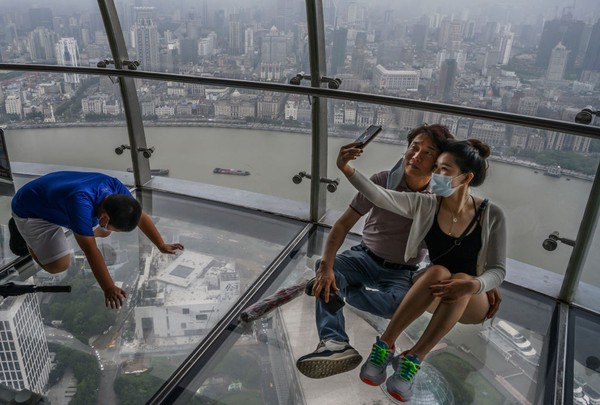 Pengunjung berkumpul di dek observasi di Menara Televisi Oriental Pearl yang menghadap ke Sungai Huangpu di distrik Pudong di Shanghai, China.
