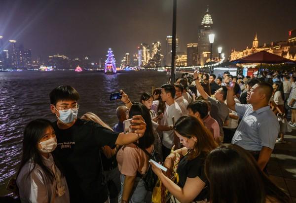 Orang-orang memenuhi sepanjang Sungai Huangpu saat cakrawala kota di distrik Pudong terlihat di Shanghai, China.