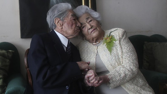 Married couple Julio Mora Tapia, 110, and Waldramina Quinteros, 104, both retired teachers, pose for a photo at their home in Quito, Ecuador, Friday, Aug. 28, 2020. The couple is recognized by the Guinness World Records as the oldest married couple in the world, because of their combined ages. They have been married for 79 years. (AP Photo/Dolores Ochoa)