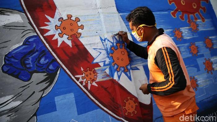 Petugas PPSU Bukit Duri menyelesaikan pembuatan mural yang berisi pesan waspada penyebaran virus Corona di kawasan Bukit Duri, Jakarta, Senin (31/8/2020). Mural tersebut dibuat agar meningkatkan kepatuhan masyarakat dalam menerapkan protokol kesehatan saat beraktivitas karena masih tingginya angka kasus COVID-19. Jumlah kasus harian Corona di DKI Jakarta pada minggu 30 Agustus 2020 memecahkan rekor dan menembus lebih dari 1.100 kasus per hari.