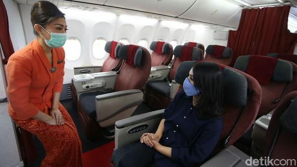 Seorang pramugari bertugas dengan mengenakan masker saat menyapa penumpang yang berada di atas pesawat terbang tersebut.