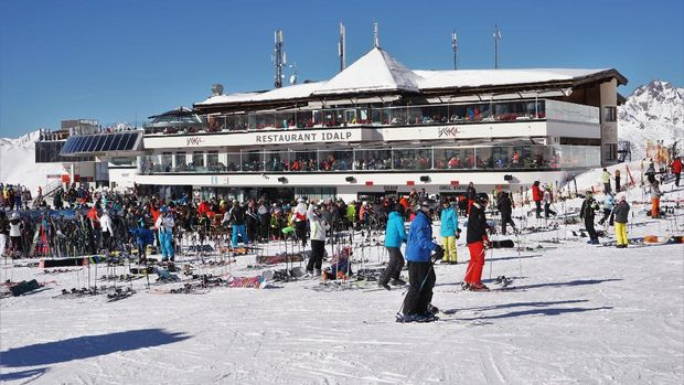 Ischgl, Austria - 7 February 2020: View of the busy Restaurant / cafe and lift station of Idalp in the Ischgl part of the Ischgl - Samnaun ski area which straddles Austria and Switzerland. Several diners are eating in the sunshine on the balcony areas.