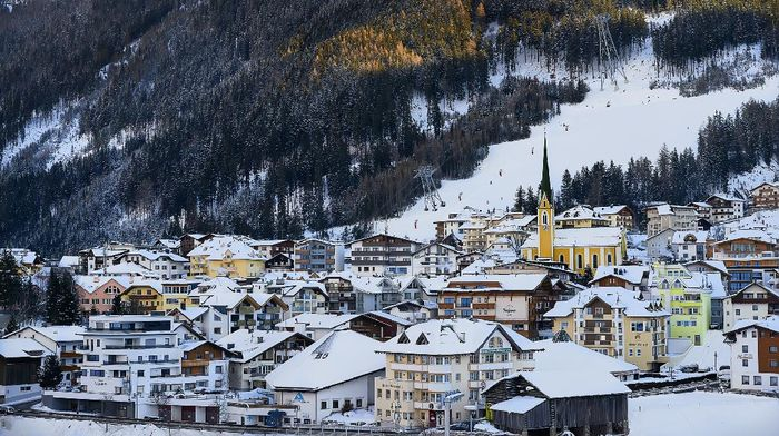 Ischgl, Austria - December 29, 2017: Ischgl in nightfall, view from hill top. Evening in small town in Tyrol Alps. The hole town is snow covered. Yellow church in the city center is a bright spot on white hill slope
