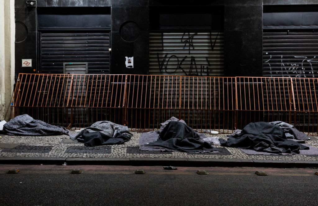 SAO PAULO, BRAZIL - AUGUST 28: A homeless person sleeps in the sidewalk next to a closed shop at the city centre on August 28, 2020 in Sao Paulo, Brazil. According to an official survey by the Municipality of Sao Paulo, homelessness increased 53% in the capital city over the last five years, reaching a total of more than 25,000 homeless people. Due to the pandemic, unemployment is rising and the number of people living on the streets has increased considerably. The situation worsens during winter with intense cold at night as two deaths have already been recorded. Many of these homeless people prefer staying on the streets rather than going to shelters for fear of contracting coronavirus (COVID-19), and survive only with the help of NGOs and social projects that donate blankets, clothing and food. (Photo by Alexandre Schneider/Getty Images)