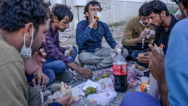 Migrants eat as they shelter next to the Tatvan bus station waiting to take a bus to travel to western Turkey, following their 200 kilometer walk from the Iranian border to Tatvan, on the western shore of Lake Van in Bitlis province on August 24, 2020. - Gravestones scribbled with identity numbers are all that remain of dozens of migrants aboard a boat that sank in a Turkish lake as they struggled to make it to Europe. Lake Van, a vast body of water nearly seven times the size of Lake Geneva, has become a death trap for Afghan, Pakistani and other migrants seeking security and work.The sinking of two boats in June and last December, claiming 68 lives in all, underscores the perils of a route they use to circumnavigate checkpoints set up across the rugged eastern terrain of Turkey, not far from Iran. Hiding on the boat with 60 others that sank on June 27 was Mehdi Mosin, then just 17. (Photo by BULENT KILIC / AFP)