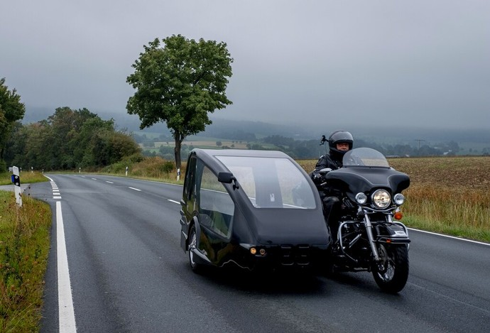 Joerg Grossmann drives his motorcycle combination with a Harley E Glide fitted with a sidecar on a road near Anspach, Germany, on Monday, Aug. 31, 2020. The 56 year old Grossmann who calls himself a chauffeur for the deceased, developed his motorbike hearse for die-hard bikers who want a last ride to their final resting place. in Frankfurt, (AP Photo/Michael Probst)