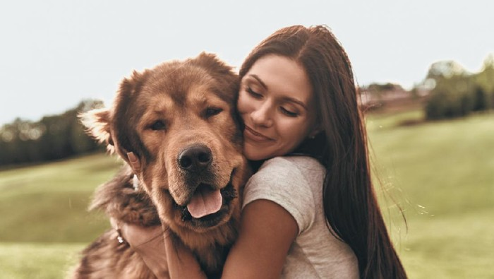 Woman cuddles, plays with her dog at home because of the corona virus pandemic covid-19