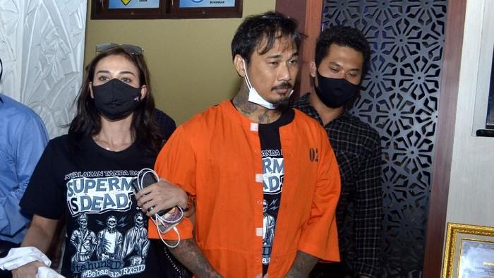Drummer Superman is Dead I Gede Ari Astina alias Jerinx (kiri) dikawal petugas disela menjalani pemeriksaan di Polda Bali, Denpasar, Bali, Selasa (18/8/2020). Jerinx kembali menjalani pemeriksaan lanjutan sebagai tersangka kasus dugaan ujaran kebencian dan pencemaran nama baik yang dilaporkan Ikatan Dokter Indonesia (IDI) Bali. ANTARA FOTO/Fikri Yusuf/pras.