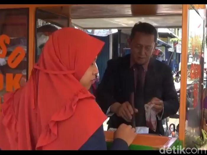 Seorang penjual bakso di Jember berpenampilan ala pengusaha untuk menarik pembeli. Pria ini tampil rapi mengenakan jas, dasi hingga sepatu pantofel.